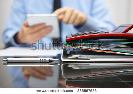 stock-photo-files-and-folders-and-businessman-in-background-with-tablet-pc-in-hands-235567633