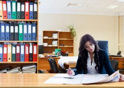 woman reading a newspaper in an office