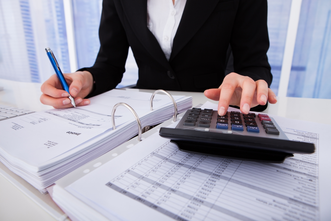 working on paperwork with a calculator